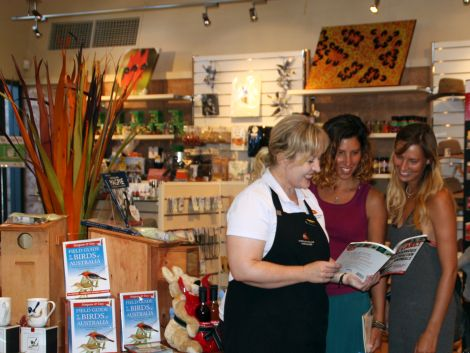 AALBG's Bernie Reichstein helps two visitors select a book in the Gift & Garden Shop